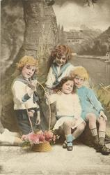 untitled: three boys & a smaller girl sit posed with a fake tree, basket of flowers held at arms length by the girl and one boy