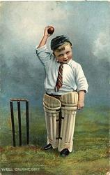 WELL CAUGHT SIR!  Boy in cricket gear hollds up ball in his right hand