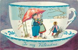 girl kisses boy's face left under umbrella, other girl right carrying twigs, looks away