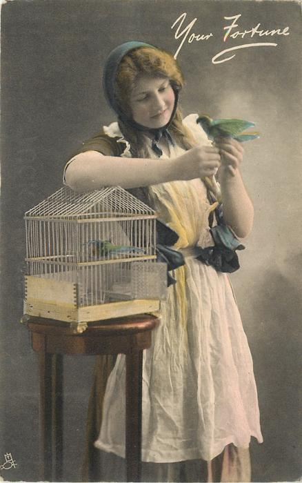 girl with long pig tails leans on birdcage with her right arm, holds bird in left hand