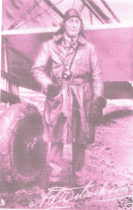 pilot A.L. WILCOCKSON standing by airplane wheel