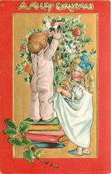 A MERRY CHRISTMAS  at top, two children decorate Christmas tree, boy standing on books