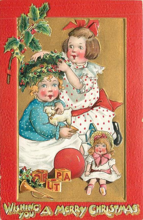 WISHING YOU A MERRY CHRISTMAS   girl puts holly wreath on head of another, doll & toys below
