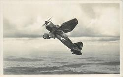 WESTLAND LYSANDER, SEEN ZOOMONG STEEPLY AN ARMY CO-OPERATION MONOPLANE WITH FULL HANDLEY PAGE SLOT EQUIPMENT ENABLING IT TO OPERATE FROM SMALL AERODROMES. HOOK FOR PICKING UP MESSAGES CAN BE SEEN BENEATH THE FUSILAGE