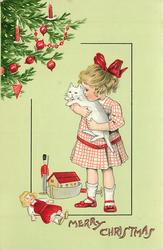 MERRY CHRISTMAS  girl holds white cat, toys around her feet, tree upper left