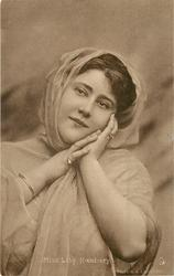 MISS HILDA HANBURY hands clasped at  her face, scarf over hair