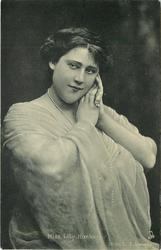 MISS LILY HANBURY  hands clasped at her face, string of pearls