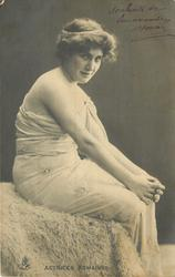 actress sits facing right, looking front, hands clasped over knees