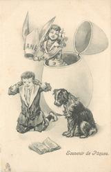 girl in huge egg holds dunces ANE cap above boy kneeling on ground, dog observes
