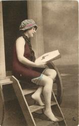 girl in bathing suit & cap sits on top step of bathing hut, looking down at a magazine