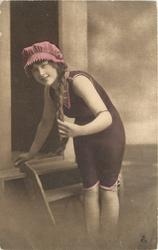 girl in bathing suit & cap stands at front of bathing hut, her left hand holds her long braid, right hand touches floor of hut