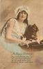 girl with frilly cap & bare arms holds pekingese on pillow, right hand touches dog, left arm cuddles dog
