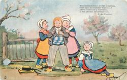 four Dutch children, two girls stand, holding either side of boy centre, another girl right sits on ground
