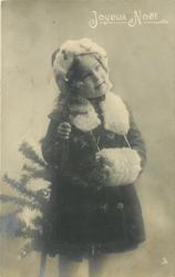 young girl dressed for winter with fur cap, cape & muff, stands facing slight right, tree on her right side, she holds near tip