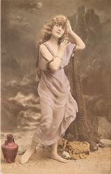 girl in robe stands posed against beach background, she faces forward right, looking up to left,holding net to her left shoulder with right hand, jug on ground to left
