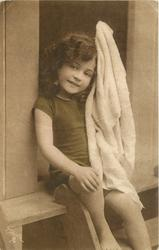 young girl in bathing costume in door of bathing hut, she sits in door holding towel up with her let arm