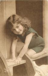 young girl in bathing costume squats in door of bathing hut arms forward to left, hands flat on top step