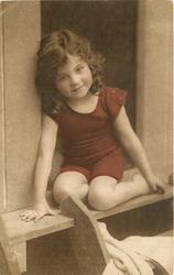 young girl in bathing costume in door of bathing hut, she sits in door with legs folded under her