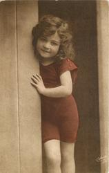 young girl in bathing costume stands in door of bathing hut with her right arm visible. hand touches side of door