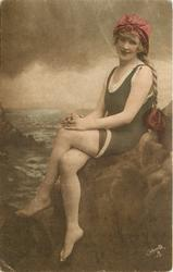 girl in bathing suit & hat sits on rocks, legs crossed left over right, hands on knees, braid hangs down her back, faces left & looks forward