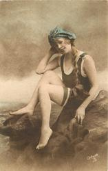 girl in bathing suit & hat sits on rocks, braid hangs on her left, faces left & looks forward