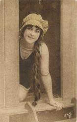 girl in bathing suit  & cap sits in door of bathing hut, she looks out with braid hanging down