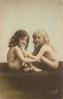 two nude children, both sitting towards each other, both look forward