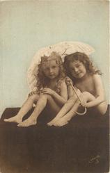 two nude children, both sitting under umbrella and look forward
