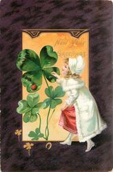 NEW YEAR GREETINGS  girl in white coat writes on exaggerated  four leaf clover heavy purple border