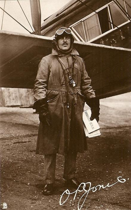 pilot  O.P. JONES standing in front of aircraft wing carrying HANNOVER BERLIN notice