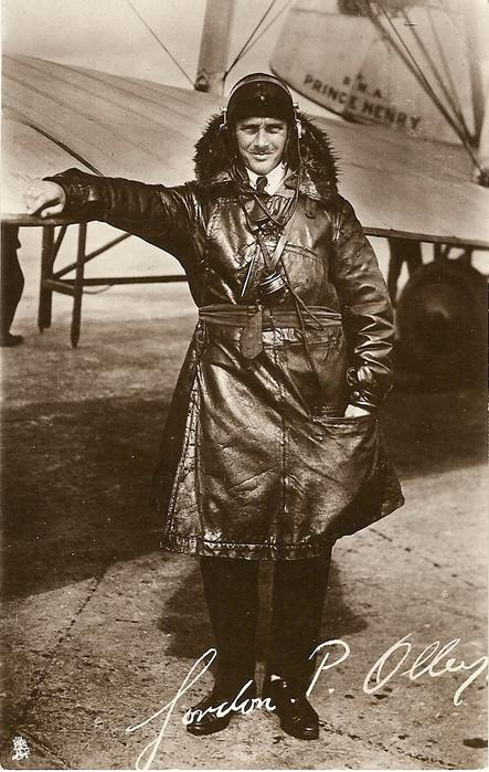 pilot GORDON P. OLLEY standing with one hand on front of aircraft wing