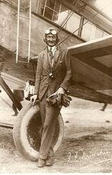 pilot F.F. MINCHIN standing in front of wheel and aircraft wing