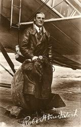 pilot ROBERT H. McINTOSH standing against wheel of aircraft