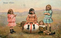 girl sits on enormous Easter egg in wheelbarrow, 3 more girls surround