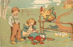 FROHLICHE OSTERN boy observes young girl paint Easter eggs, rooster & hen on fence