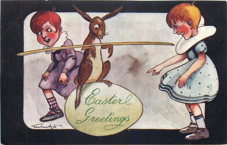 EASTER GREETINGS  bunny plays on yellow egg with long stick in arms while two girls watch