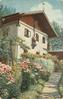 path with many flowers, building behind adorned with elk head, warrior statue, flag and cross