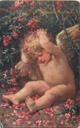 A LOVE TOKEN (gilt) cherub with both hands behind head sits under rhododendron bush, many red flowers around