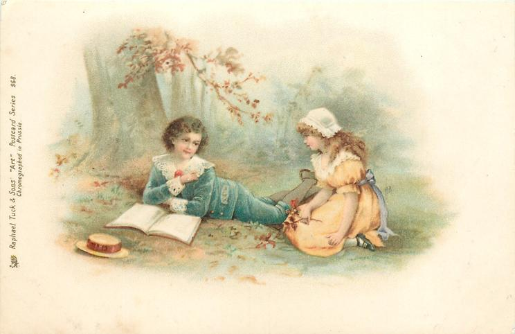 boy lies with book open in front looking at girl, beneath tree