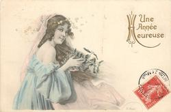 girl with long hair in off-shoulder dress faces right, glancing front, holding mistletoe in her hands