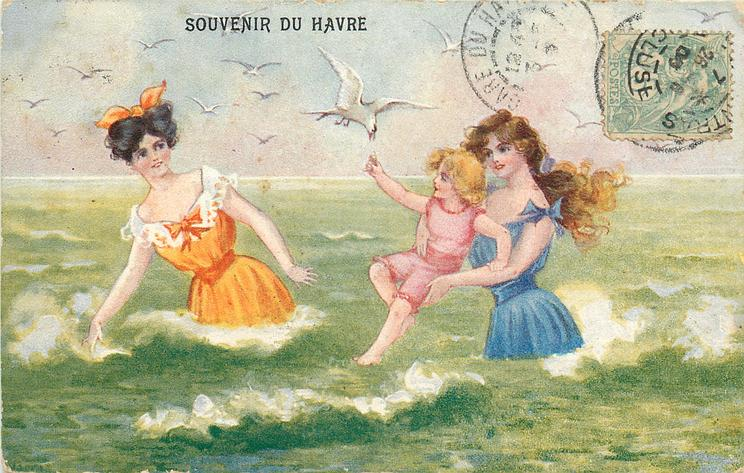 2 girls & one child in old-style bathing dresses, child lifts hand to seagull
