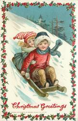 CHRISTMAS GREETINGS  girl sits behind boy on toboggan coming downhill