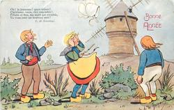 three Dutch children, girl in centre loses her bonnet to the wind