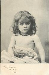 young girl sitting, holding fake bird on lap, looking cross, beads around neck