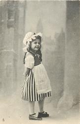 girl in vertically striped skirt stands facing right