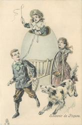 girl drives boy pulling huge egg on cart, girl follows, dog runs alongside