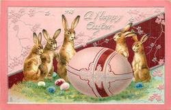 A HAPPY EASTER 5 bunnies on hind legs, giant egg in centre, 6 smaller eggs saround