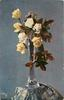 yellow roses, four in bloom, in tall glass vase with slender neck