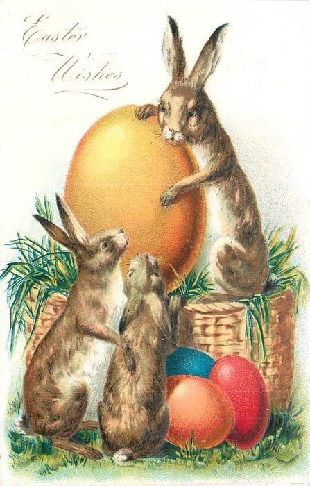 EASTER WISHES rabbit sits upright on basket holding giant yellow Easter egg, two other rabbits observe, 3 eggs on ground