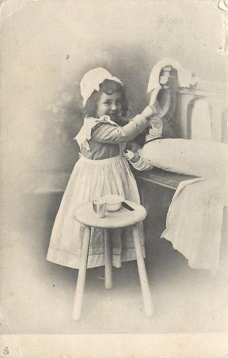 fully dressed girl in nurses uniform stands tending to prone doll right